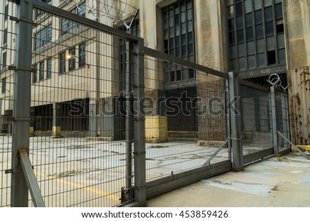 Industrial metal gate with abandoned building in background.  Chicago, Illinois, U.S.A. - stock photo