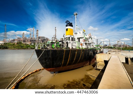 Industrial ocean ship wharf at oil refinery shipping port - stock photo
