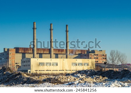 Industrial old building in winter time with tree funnels over blue sky in Belarus. - stock photo