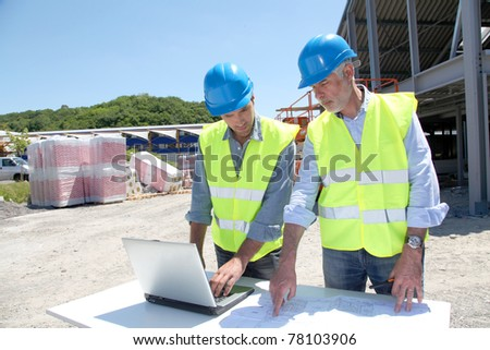 Industrial people working on building site - stock photo