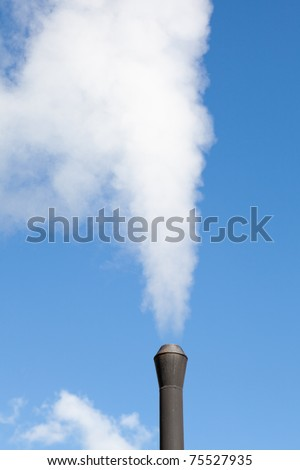 Industrial pipe polluting white steam on the blue sky background