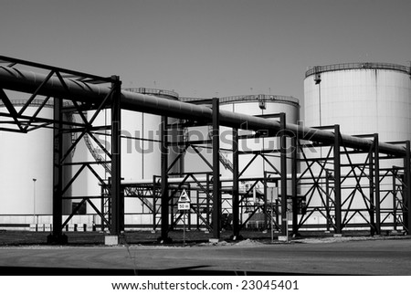 industrial pipelines and storage tanks against blue sky  b&w
