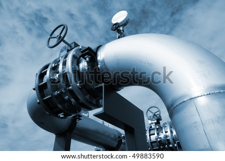industrial pipelines and valve on pipe-bridge against blue sky - stock photo