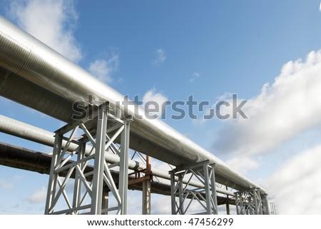 industrial pipelines on pipe-bridge against blue sky. - stock photo