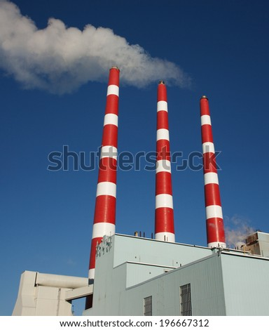 Industrial plant smoke stacks and blue sky. - stock photo