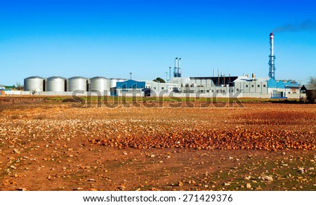 industrial plant with store buildings near field  under clear blue sky  - stock photo
