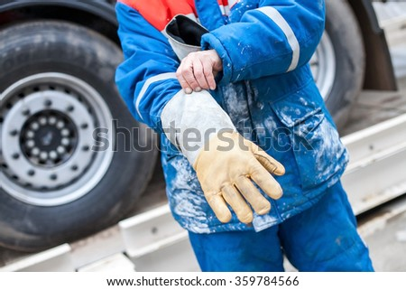 Industrial protective clothing, gear. The worker puts on a protective glove. Worker's gloves closeup. Worker's hands closeup.   - stock photo