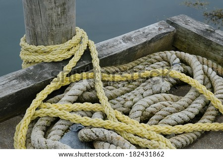 Industrial rope on a dock in knots - stock photo