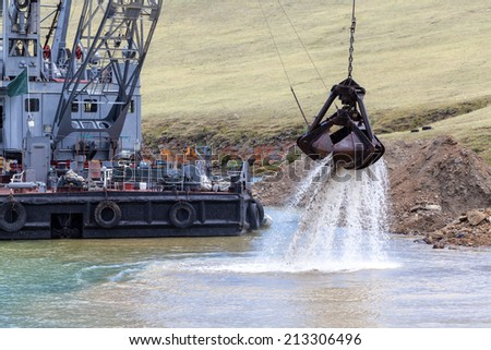 Industrial ship crane digs sand from water - stock photo