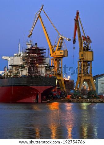 Industrial shipyard yellow crane at night. - stock photo