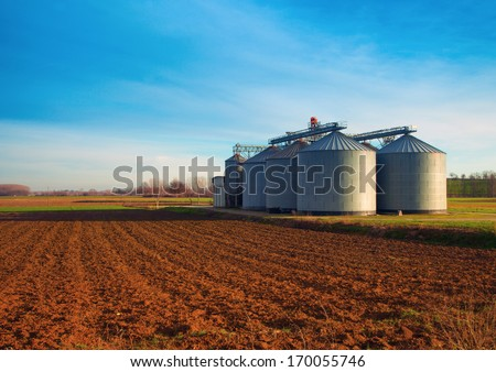 Industrial silos in the fields, in the sunset - stock photo