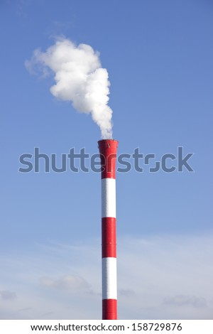 Industrial smoking chimney at the blue cloudy sky