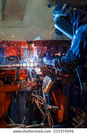 Industrial steel welder in factory - stock photo