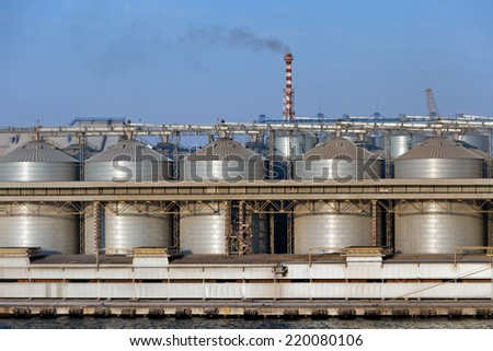 Industrial storage background - big metallic tanks, containers in sea port, pipe with smoke - stock photo