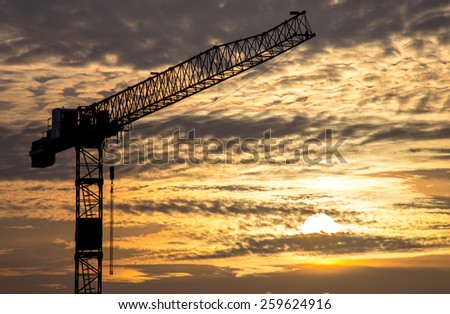 Industrial sunset with construction crane - stock photo