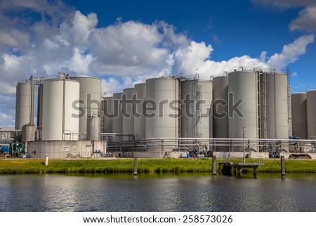 Industrial Tank Storage area with docking facility in a harbor in the Netherlands - stock photo