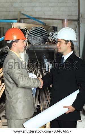 Industrial theme: two businessman shaking their hands at a manufacturing area. - stock photo