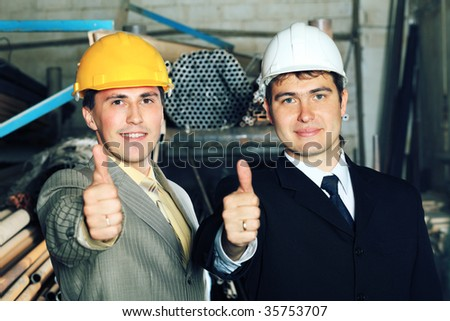Industrial theme: two businessman showing good results at a manufacturing area. - stock photo