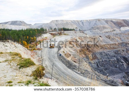Industrial truck moves along the road in the sand quarry - stock photo
