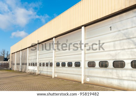 industrial unit with old and damages roller shutter doors - stock photo