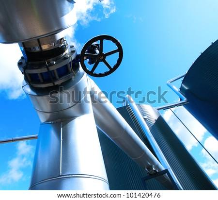 industrial valve against blue sky - stock photo