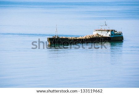 Industrial vessel - bulk-carrier on sea background. Cargo ship sailing with sand heaps. - stock photo
