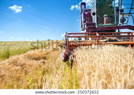 industrial vintage harvesting machinery in wheat crops. Rural agriculture and farming with vintage machines - stock photo