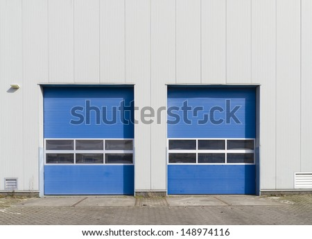 industrial warehouse with double blue roller doors - stock photo