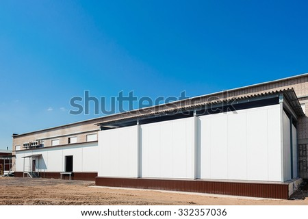 industrial warehouse with office unit with blue sky - stock photo