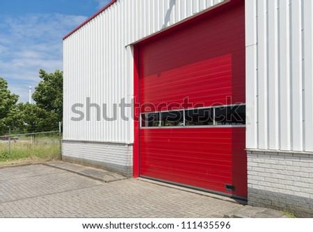 industrial warehouse with red roller door - stock photo
