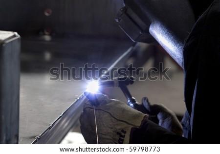 Industrial welder welding on steel in factory - stock photo