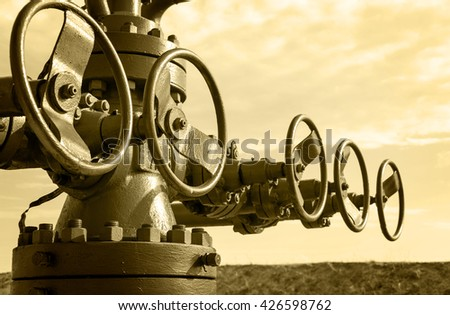 Industrial wellhead with valve armature. Oil, gas theme. Toned sepia. - stock photo