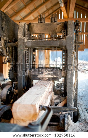 industrial wood factory - industrial saw cutting logs  - stock photo