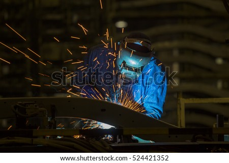 Industrial Worker at assembly line in car factory is welding automotive part