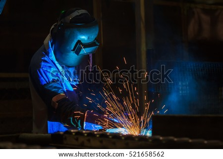 Industrial Worker at the factory welding assembly automotive part with protective mask,close up