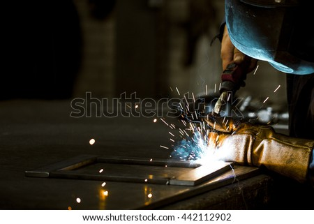 Industrial worker cutting and welding metal with sharp sparks - stock photo
