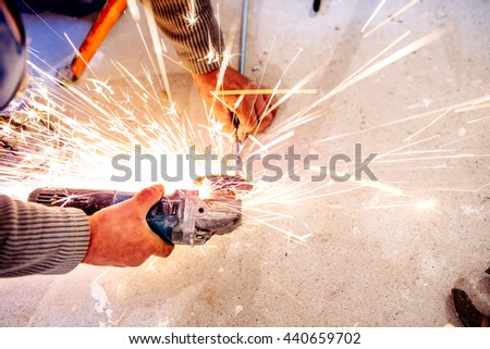 industrial worker cutting steel with metal grinder - stock photo