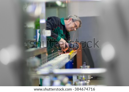 Industrial worker in manufacturing plant grinding steel structure. Sparks from grinding machine in workshop. Industrial background, industry. - stock photo