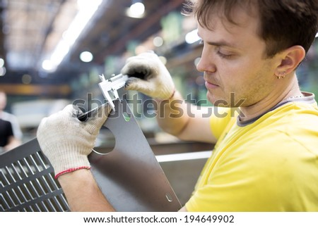 Industrial Worker Inspector Measuring detail with Vernier Caliper in Factory Workshop - stock photo