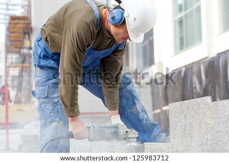 Industrial worker making horizontal cut with electric hand saw during align marble tiles at construction site - stock photo