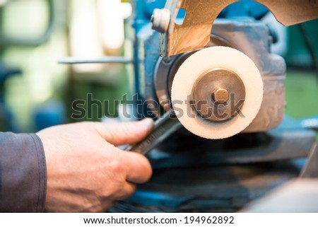 Industrial worker mounting abrasive disc at grinding machine in factory workshop - stock photo