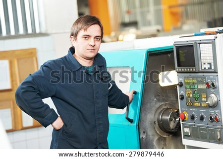 industrial worker near cnc milling machine center at factory tool workshop - stock photo
