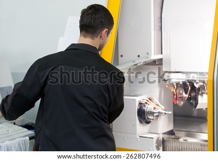 Industrial worker operator working for the computerized lathe CNC machine at factory workshop - stock photo