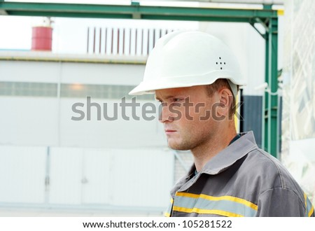Industrial Worker, serious looking, controls work in a factory - stock photo