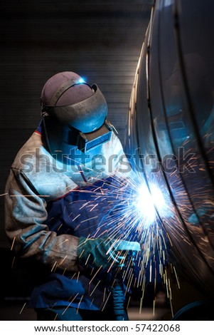 Industrial worker welding in factory - stock photo