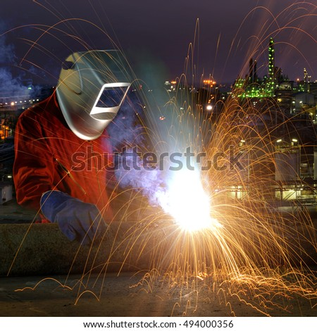 Industrial worker welding metal with many sharp sparks and worker during use electric wheel grinding