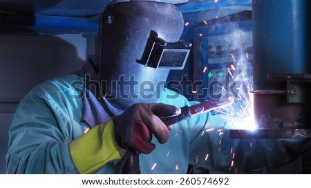 Industrial worker welding steel pipe flange,a spark welding. - stock photo