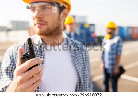 industry, building, technology and people concept - close up of male builder in hardhat with walkie talkie or radio outdoors - stock photo