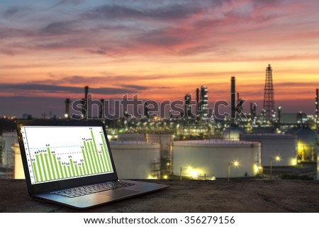 Industry business concept idea, laptop on wooden table with oil refinery background - stock photo