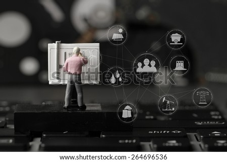 industry concept-miniature engineer working with drafting table on laptop computer with industry diagram - stock photo